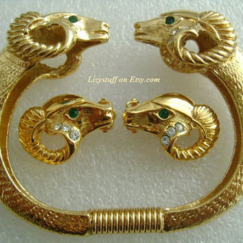 KJL For AVON Rich Gold Tone Two-Headed Face to Face Ram Clamper Bracelet and Matching Rams Head Earrings With Clear & Green Rhinestone Eyes