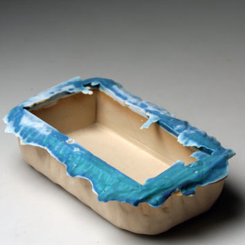 White stoneware clay container with turquoise rim