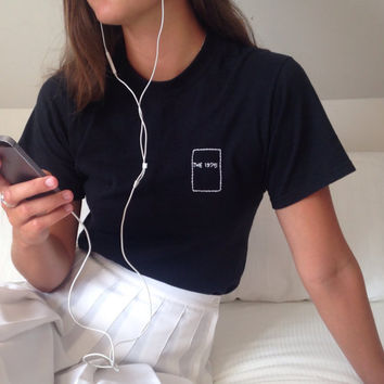 The 1975 logo hand embroidered on a small, black t-shirt.