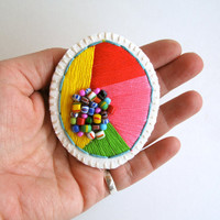Hand embroidered jewelry geometric brooch bright colors of red yellow pink and green with African beads on cream muslin with cream felt back