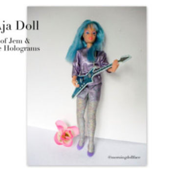 Aja Doll of the Jem Collection. 1986. Blue hair, guitar, shoes, leather skirt.  Hasbro co.