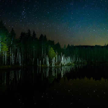 Stars in the night sky reflecting in Deception Pond at night, in White Mountain National Forest, New Hampshire.