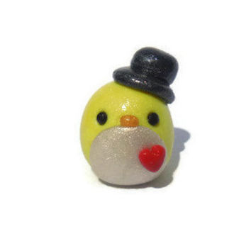 Miniature polymer clay penguin sculpture, yellow penguin figurine, penguin wearing hat, kawaii animal sculpture.