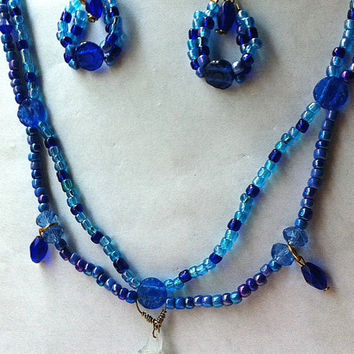Blue scalloped beaded necklace with tiny filled glass bottle