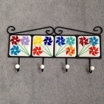 Four hook metal coat rack with four hand cut fused glass flower tiles
