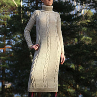 Hand knitted dress with long sleeves and high collar. Handmade cable knit. Blended beige virgin wool yarn. Ilze Of Norway