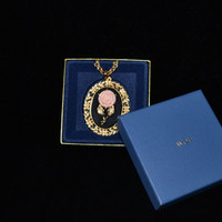 AVON Designer Vintage gold tone necklace with mirrored back and rose on black enamel pendant in original box