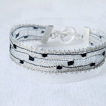 bracelet, handmade bobbin lace out of yarn, silver with black, silber coated fastener, hekate no 926