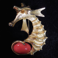 Lind Gal Seahorse Brooch clutching a coral red egg by his tail.  Whimsical Seahorse figurine  made of gold toned metal and coral lucite.