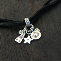 Charm necklace. Leather and sterling silver charm necklace. Soft black leather cord with mixed star and flower charms and topaz gemstone.