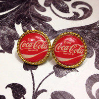Round stud Coca-Cola earrings with gold trim.