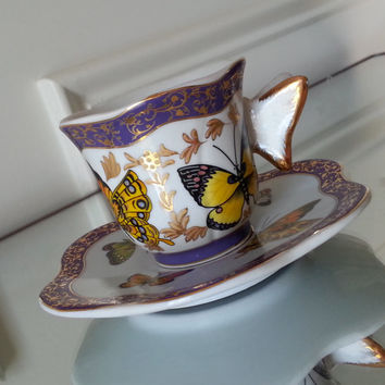 Formalities by Baum Bros butterfly handle demitasse tea cup and saucer set in pale blue with gold and purple accents