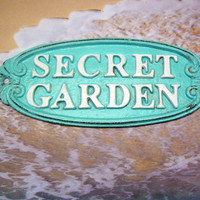 Secret Garden Wall Plaque Sign Cast Iron Cottage Blue Raised Letters Bright White Metal Oval Oblong Ornate Scroll Accented Wall Door Sign