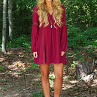 Our Hanging By A Moment Dress is stunning! It is Burgundy in Color and is super comfortable. It features long sleeves, a V Neckline and peekaboo crochet detailing down the front of the dress and on the sleeves.