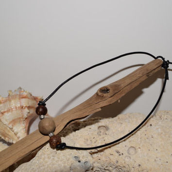 Choker with a light brown Wooden bead, two Acai beads on a black leather cord with a Lariat closure