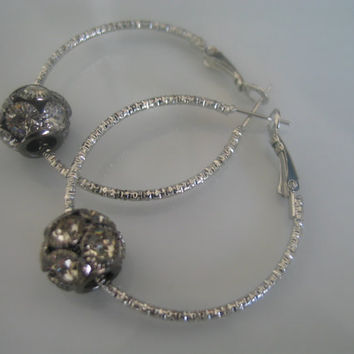 European style silver colored hoop earrings with a silver colored multi-faceted european style round diamond encrusted design bead