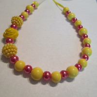 Sunny yellow plastic pearls, rosey red glass pearls and 3 plastic deco beads.