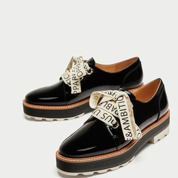 FAUX PATENT BROGUES WITH SLOGAN PRINT BOW DETAILS