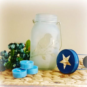 Etched bird on a frosted hanging mason jar. Tea light candle holder attached to navy blue lid with a star punched out on top.