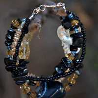 Multi-strand bracelet with Onyx, Citrine, and Black Agate stones plus crystals with a gold filled wire clasp.