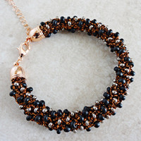 Knitted bracelet in auburn color lurex yarn and seed beads
