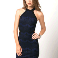 Sleeveless Lace Cutout bodycon Dress featuring black textured lace fabrication, sleeveless, mock turtleneck with single button closure, side cutout at the waist, open back with straps detailing, and back zipper closure. Unlined.