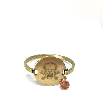 We would love to tell you a little bit about Top Shelf brand jewelry line so you may appreciate the wonderful handcrafted Engraved Skull & crossbones vintage brass locker tag cuff with a dainty copper color penny you are looking at! This is a costume jewel