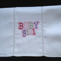 Baby Girl embroidered in pink, green, purple on a burp cloth. The seams have decorative stitches. Can be personalized for an extra charge.