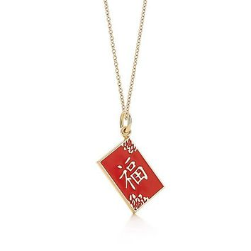 "Tiffany & Co. -  Chinese ""Wealth"" charm in 18k gold with red enamel finish. On a chain."