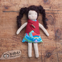 Waldorf inspired ragdoll with curly brown hair and a cute red vest