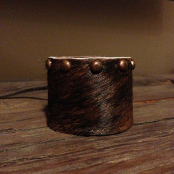 Dark hair on cuff with rustic copper spots with an adjustable old fashioned leather button