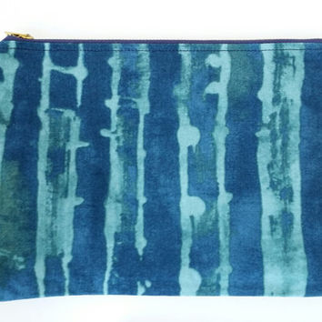 Oversized Teal And Dark Blue Zipper Pouch With Vertical Abstract Lines And A Pinkish Red With Taupe Lining And Navy Metal Zipper