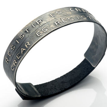 Double silver and leather bracelet with a message in Dymo typography.