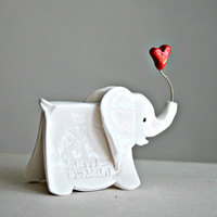 Small elephant sculpture with imprinted words of wisdom and holding a heart in his trunk.