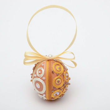 Hanging handmade decorative pendant egg with beads and threads for Easter decor
