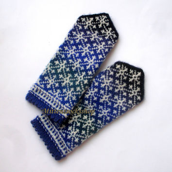 Hand knitted mittens Gloves from batic yarn White winter ornament on a blue green dark gray tinted background Patterned mittens Warm gloves