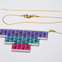 Pendant with woven embroidery floss, nylon and gold plated beads. Pastel tones.
