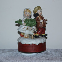 Rotating porcelain musical Christmas figurine, boy and girl cutting down tree, holiday decor, collectible figurines