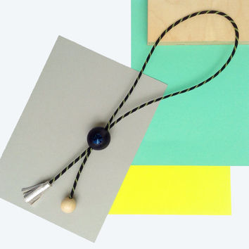 chunky rope statement necklace featuring bold beads with blue gemstone bolo tie style