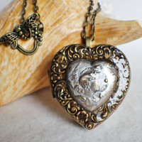 Music box locket, heart shaped locket with music box inside, with Victorian maiden and etched heart border on front cover.