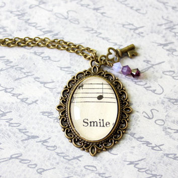 Victorian style sheet music necklace with skeleton key charm and ombre purple crystals.