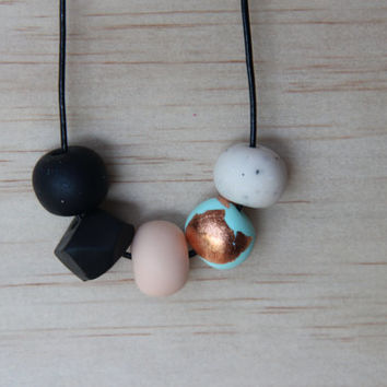 No. 53- Handmade polymer clay beads featuring black, black geo, flesh pink, mint with copper leaf and marble beads on black leather