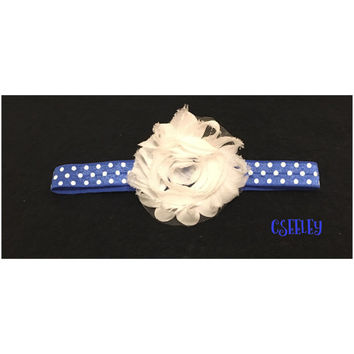 blue headband with white polka dots and white flower