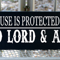 This house is protected by the good lord and a gun wood sign
