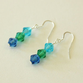Earrings made from different shades of aqua glass beads with silver earwires.