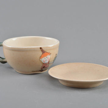 Children's handmade cup and saucer made of porcelain painted with colored glaze