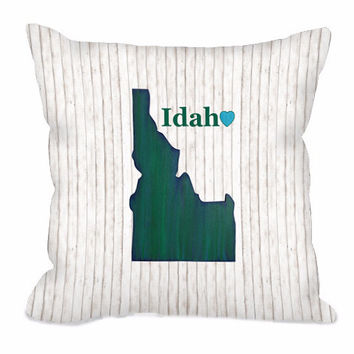 Idaho State Throw Pillow in green and blues on a rustic white wood background