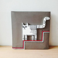 White cat wall hanging, porcelain cat in grey background, square wall tile of stoneware and porcelain, cat descending stairs, cat art object