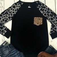 Black top with a gold sequin pocket with cheetah print sleeves.