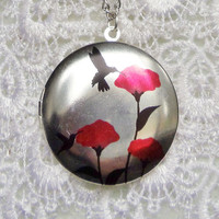 Round locket with hummingbirds and poppies on front cover adorned with fresh water pearls and silver accents